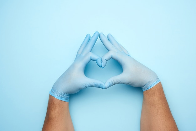 Twee mannelijke handen in blauwe latex steriele medische handschoenen toont een gebaar van het hart, concept van goedheid, hulp en vrijwilligerswerk