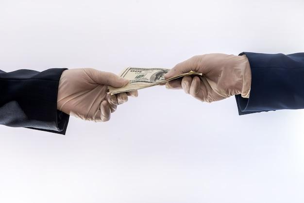 Twee mannelijke handen in blauwe medische handschoenen met 100 dollar biljet, geïsoleerd