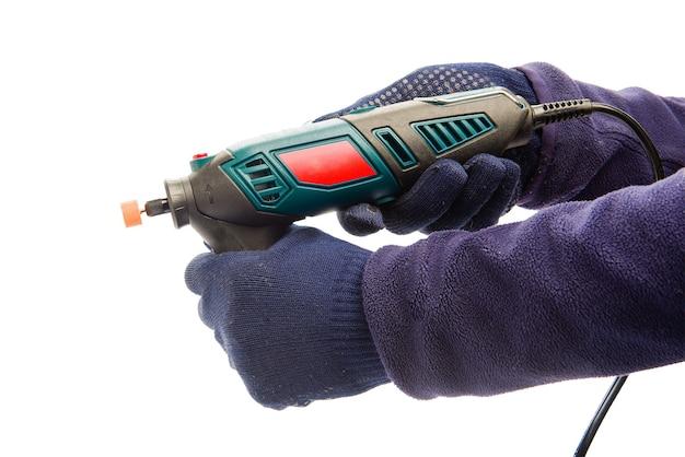 Twee mannelijke handen in marineblauwe beschermende handschoenen met perforator