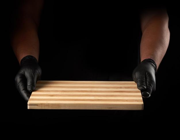 Twee mannelijke handen in zwarte latexhandschoenen houden een lege nieuwe bruine houten snijplank, zwarte achtergrond