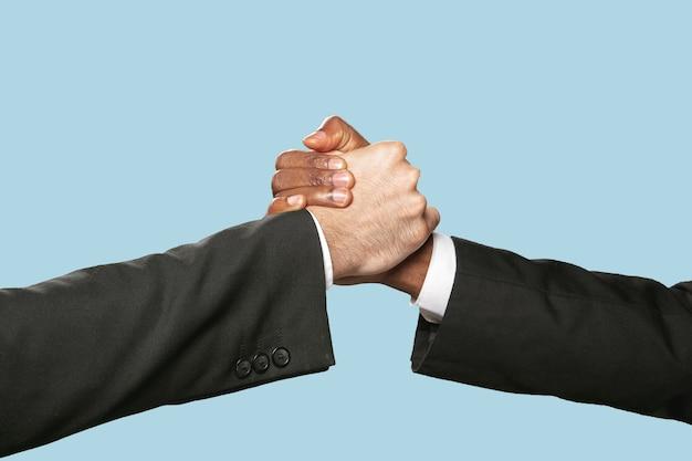 Twee mannelijke handen schudden geïsoleerd op blauw.