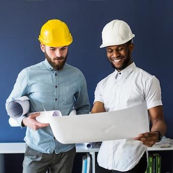 Twee mannelijke ingenieurs die blauwdruk bekijken