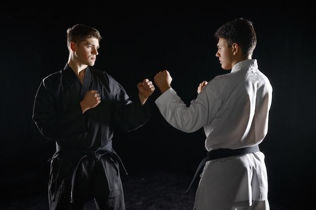 Twee mannelijke karateka's in witte en zwarte kimono, staking. vechters op training, vechtsporten, vechtwedstrijden