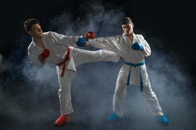 Twee mannelijke karateka's in witte kimono en handschoenen staken in actie. vechters op training, vechtsporten, vechtwedstrijden