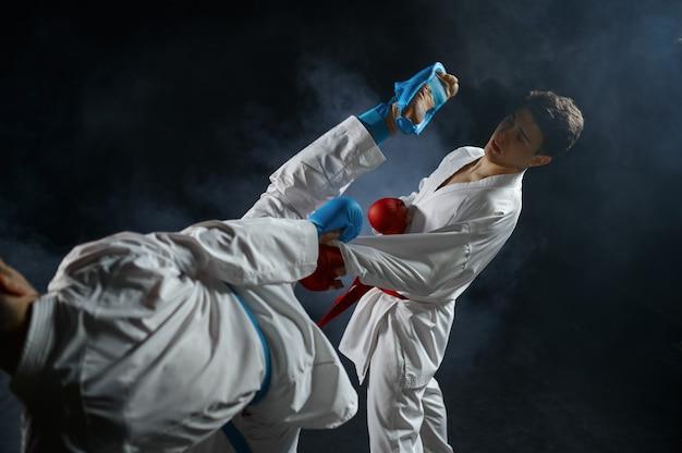 Twee mannelijke karateka's in witte kimono en handschoenen, vechten in actie. vechters op training, vechtsporten, vechtwedstrijden