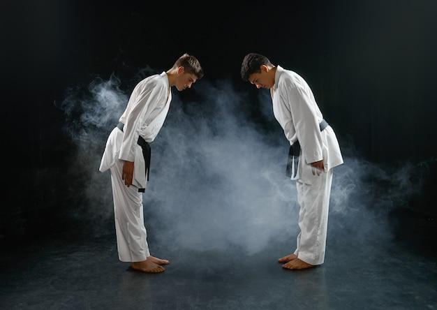 Twee mannelijke karateka's in witte kimono, gevecht. vechters op training, vechtsporten, vechtwedstrijden