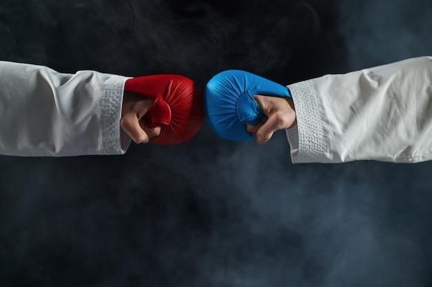 Twee mannelijke karatekas dienen handschoenen, gevechtsconcept in. vechters op training, vechtsporten, vechtwedstrijden