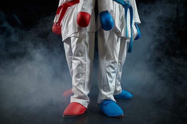 Twee mannelijke karatekas vormt in witte kimono en handschoenen, staking. vechters op training, vechtsporten