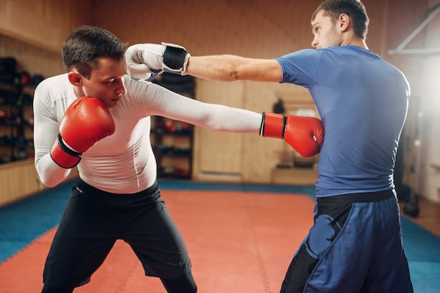 Twee mannelijke kickboksers oefenen op training in de sportschool