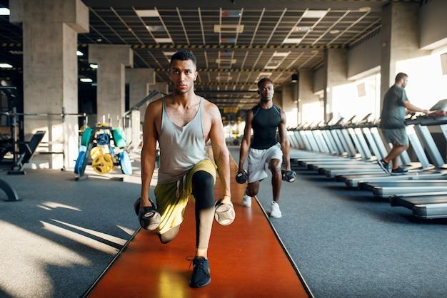 Twee mannelijke personen doen oefening met halters, trainen in de sportschool
