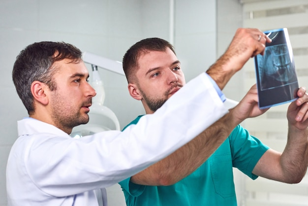Twee mannelijke tandartsen die röntgenstraal analyseren
