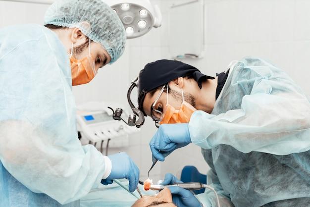 Twee mannelijke tandartsen voeren een operatie uit op een patiënt. chirurgie in de tandheelkunde. professioneel uniform en uitrusting van een tandarts. gezondheidszorg uitrusten van een artsenwerkplek. tandheelkunde