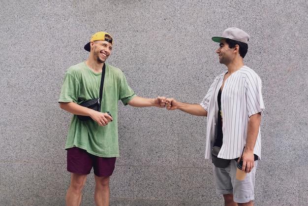 Twee mannelijke vrienden werken samen en slaan elkaars vuisten, teamwerk en vriendschapsconcept