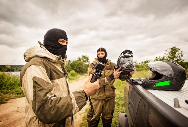 Twee mannen buiten dragen bivakmuts helmen en motorfiets uniformen.