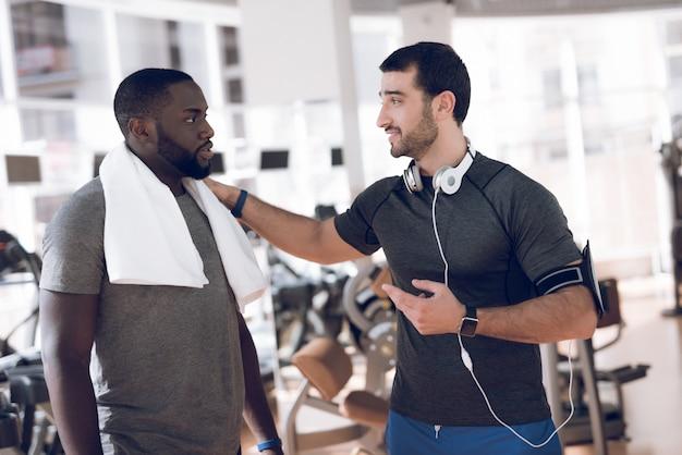 Twee mannen communiceren op de circuits in de sportschool.