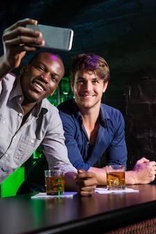 Twee mannen die een selfie op telefoon nemen bij barteller in bar