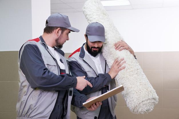 Twee mannen die groot tapijt voor de schoonmaakdienst weghalen