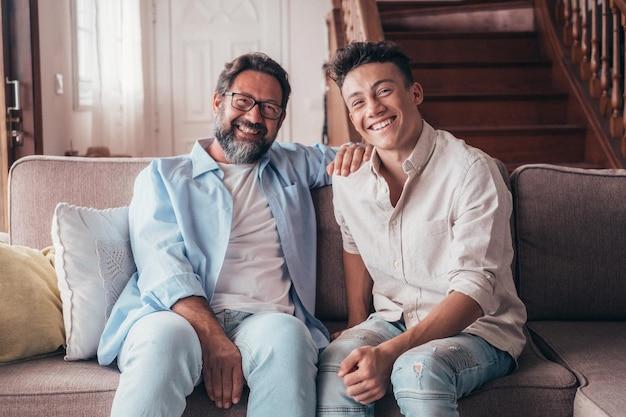 Twee mannen die samen plezier hebben op de bank, genieten van de levensstijl van thuis en lachen terwijl ze naar de camera kijken. vader en zoon relatie glimlachend binnenshuis.