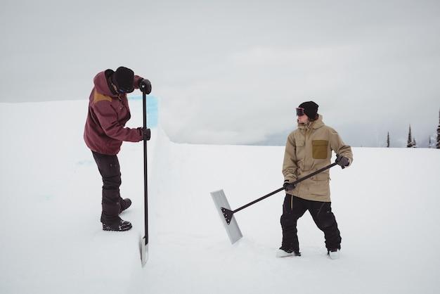 Twee mannen die sneeuw in skiresort schoonmaken