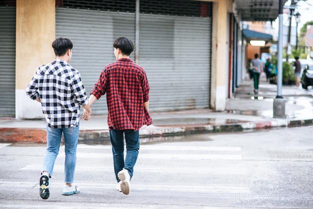 Twee mannen die van elkaar houden, houden elkaars hand vast en lopen samen.