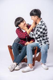 Twee mannen die van elkaar houden, knuffelen en zitten op een stoel.