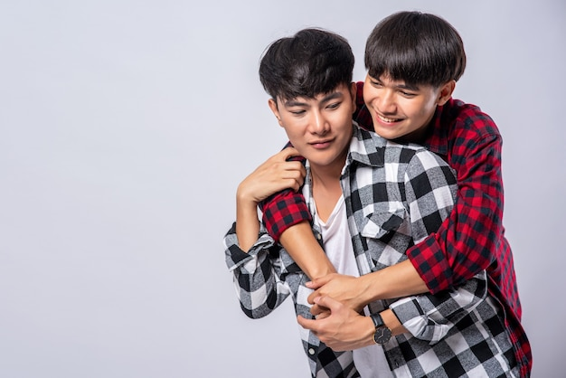 Twee mannen die van elkaar houden, knuffelen van achter elkaar.