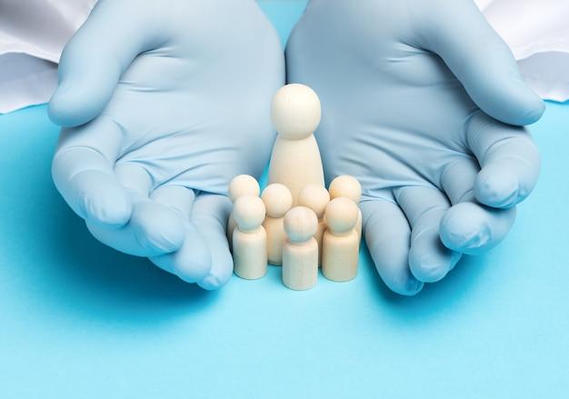 Twee mannen dienen blauwe latexhandschoenen en houten beeldjes in van een vrouw met kinderen, het concept van een groot gezin en een verzekering