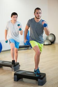 Twee mannen doen stap aërobe oefening met halter op stepper