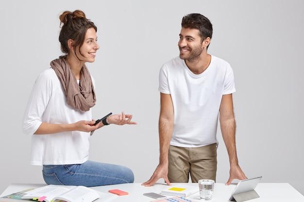 Twee mannen en vrouwen, collega's of partners, discussiëren actief over toekomstige plannen, kijken elkaar vrolijk aan