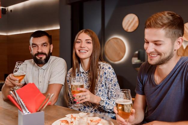 Twee mannen en vrouwen die glazen bier houden en in pizzeria zitten.