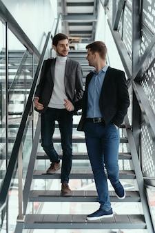Twee mannen gaan naar boven, trappen af terwijl ze kletsen