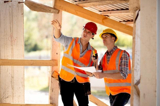 Twee mannen gekleed in overhemden, oranje werkvesten en helmen verkennen bouwdocumentatie op de bouwplaats bij de houten bouwconstructies.
