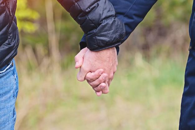 Twee mannen hand in hand in jasjes, close-up weergave