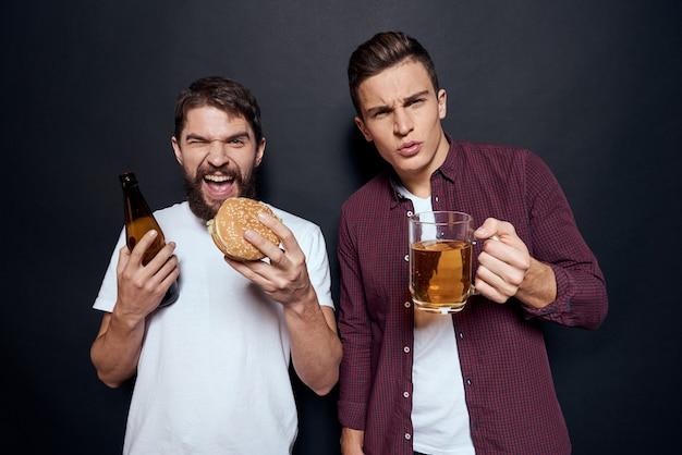 Twee mannen hebben plezier, drinken bier en eten fastfood.