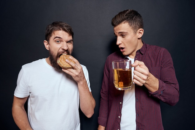 Twee mannen hebben plezier, drinken bier en eten fastfood