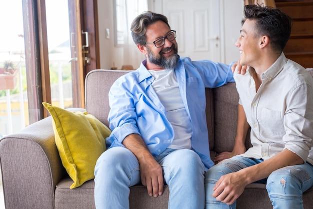Twee mannen hebben samen plezier op de bank en genieten van de levensstijl van thuis en lachen om een grappig moment. vader en zoon relatie glimlachend binnenshuis.