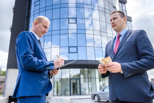 Twee mannen in pak maken buiten deal
