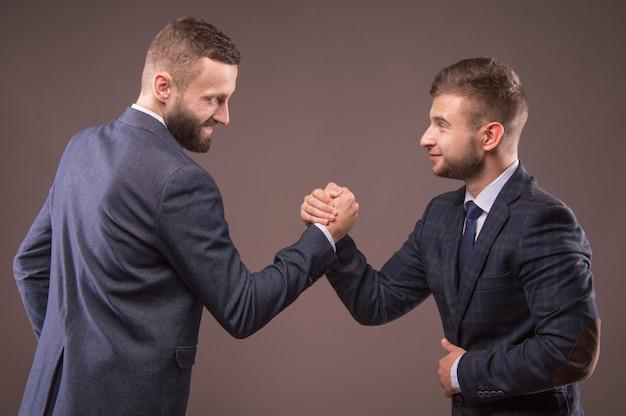 Twee mannen in pak worstelen in zijn armen en kijken elkaar in de ogen