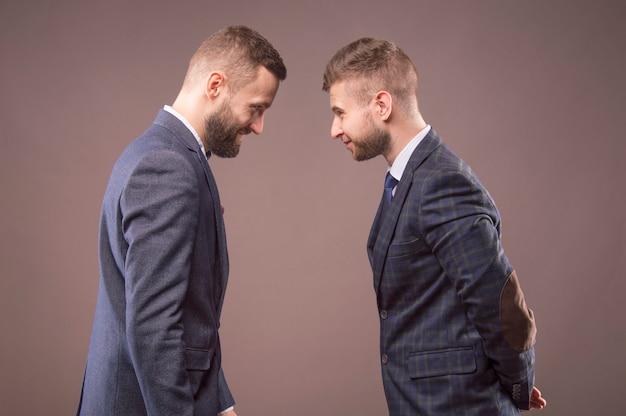 Twee mannen in pakken die elkaar stoten en glimlachen