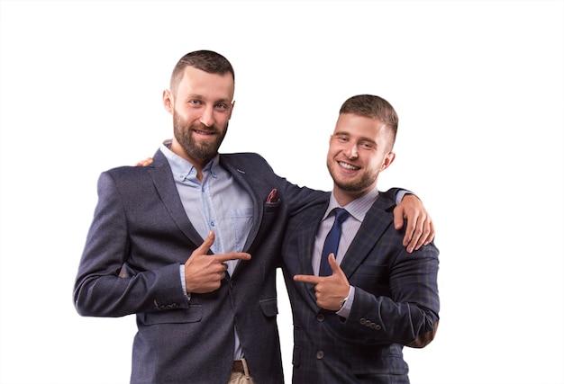 Twee mannen in pakken knuffelen elkaar en wijzen met de vinger naar elkaar