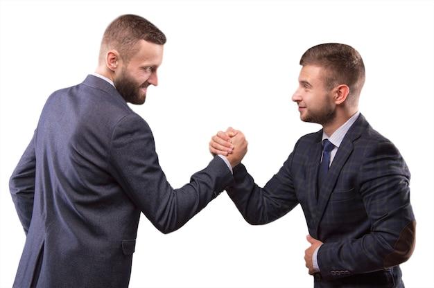 Twee mannen in pakken worstelen in zijn armen en kijken elkaar in de ogen