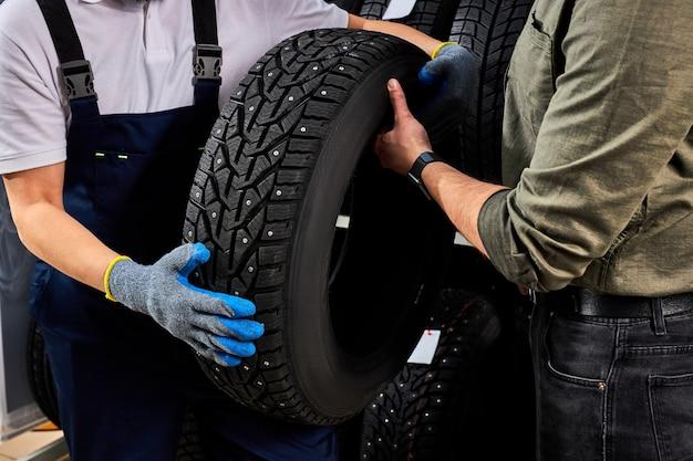 Twee mannen kijken naar het oppervlak van autobanden en bespreken de voordelen van winterbanden voor auto's, praten, raken aan en onderzoeken