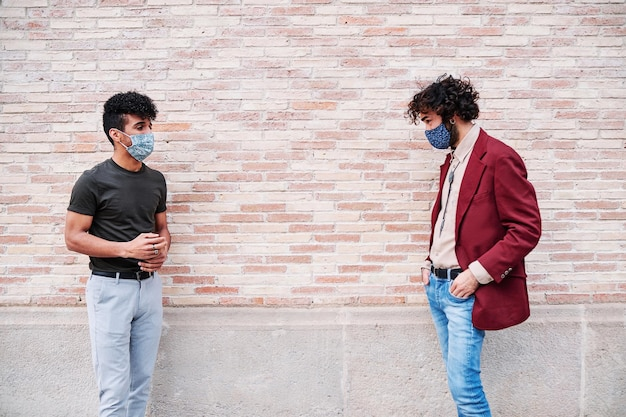 Twee mannen met beschermend masker en sociale afstand die buiten praten
