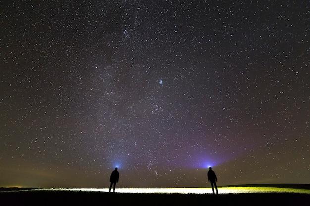 Twee mannen met hoofdflitslichten onder donkere sterrenhemel.