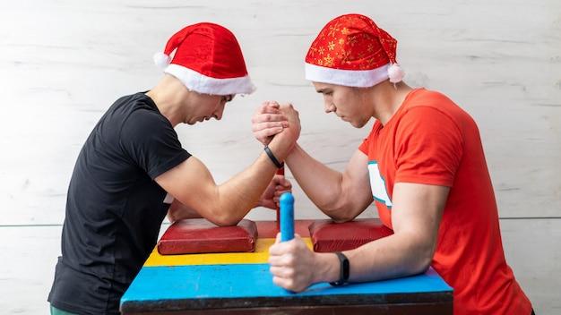 Twee mannen met kerstmutsen op arm worstelen in een sportschool
