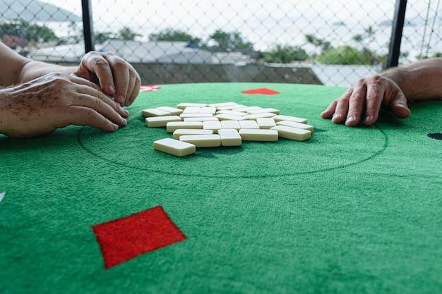 Twee mannen pakken hun stukken op om een dominospel te beginnen.