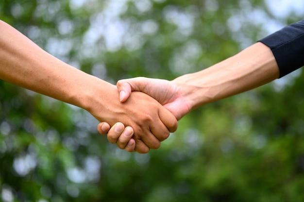 Twee mannen slaan de handen ineen om eenheid te tonen.