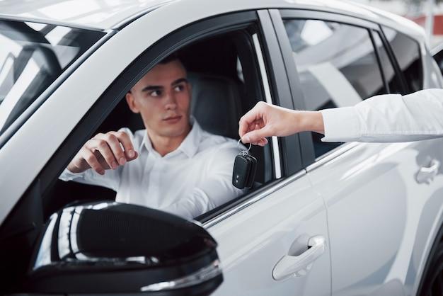 Twee mannen staan in de showroom tegen auto's. close-up van een verkoopmanager in een pak die een auto aan een klant verkoopt. de verkoper geeft de sleutel aan de klant.