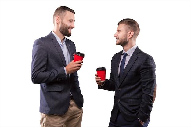 Twee mannen staan met een kopje koffie in de hand glimlachend en veroordelen een interessant onderwerp