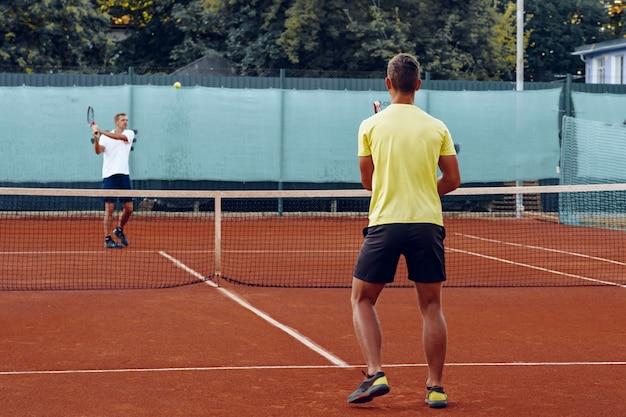 Twee mannen tennissen op het tennisveld van de klei
